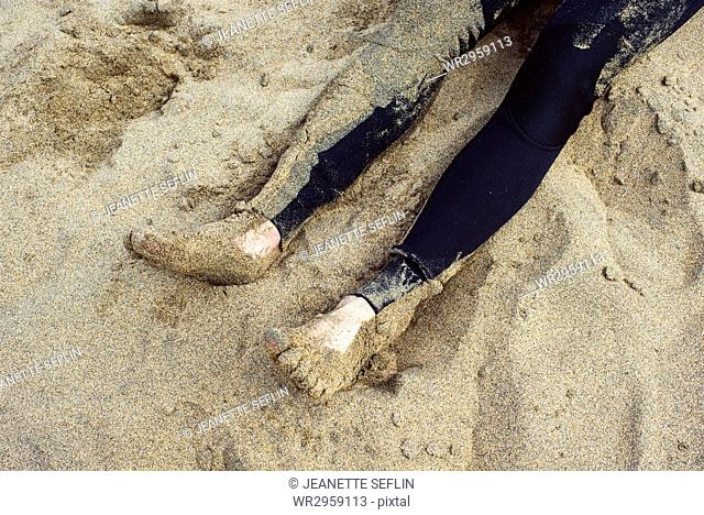 Low section of surfer lying down on beach
