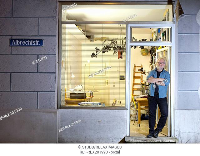 Full length portrait of designer artist standing in doorway of office