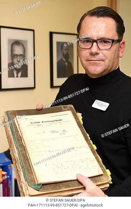 Dr. Jan Armbruster, leading senior physician of the Stralsund forensic psychiatry, holding up the Falla file from 1921 in Stralsund, Germany, 08 November 2017