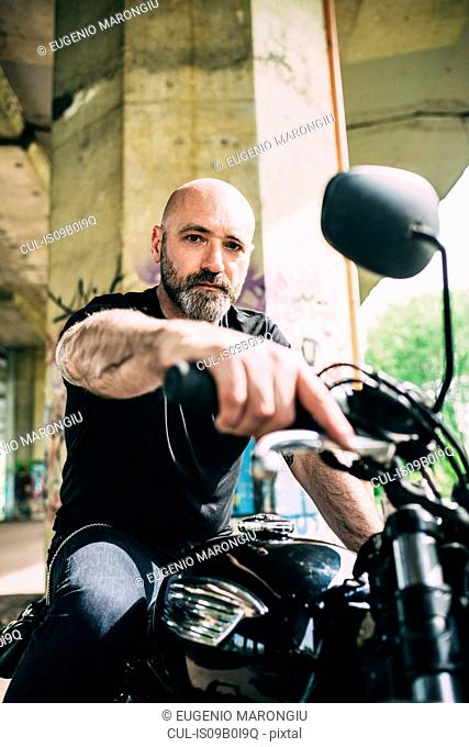 Portrait of mature male motorcyclist sitting on motorcycle under flyover