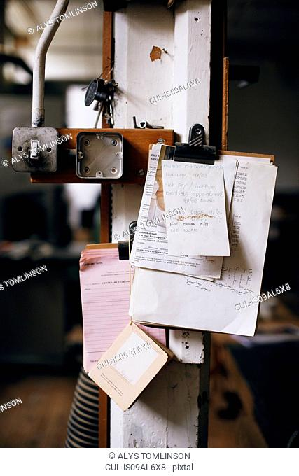 Still life of clipboard and notes on pillar in pipe organ workshop
