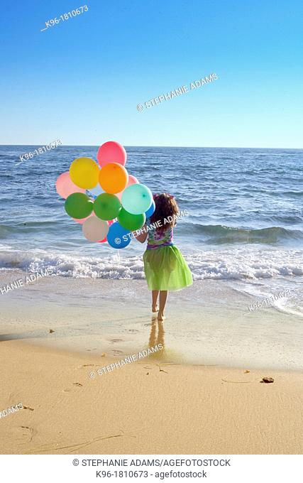 young girl walking towards the ocean with balloons with a view to see forever