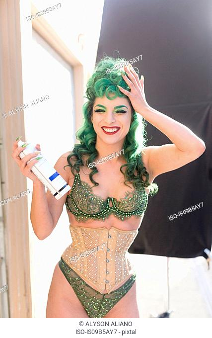 Woman with dyed green hair wearing corset using hairspray smiling