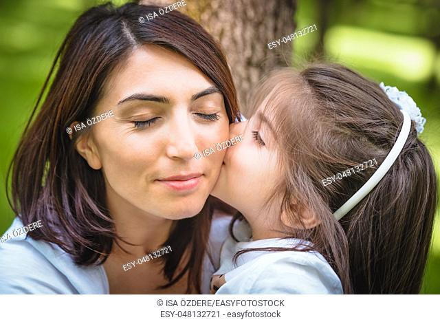 Adorable four years old cute little girl kisses her mother with love. Happy family on a summer meadow. little girl child baby daughter hugging and kissing...