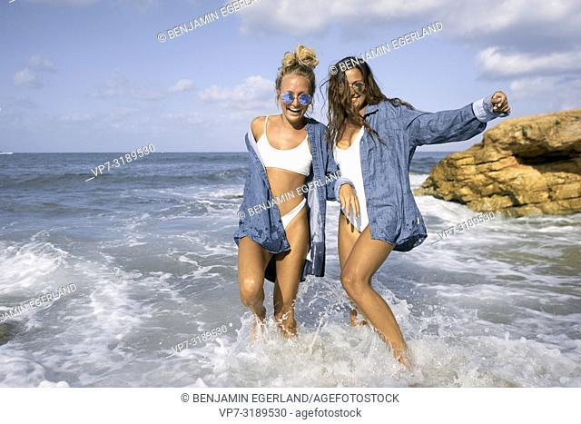 Two women walking in sea water at beach, Chersonissos, Crete, Greece