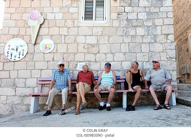 Portrait of five senior men sitting on town square bench