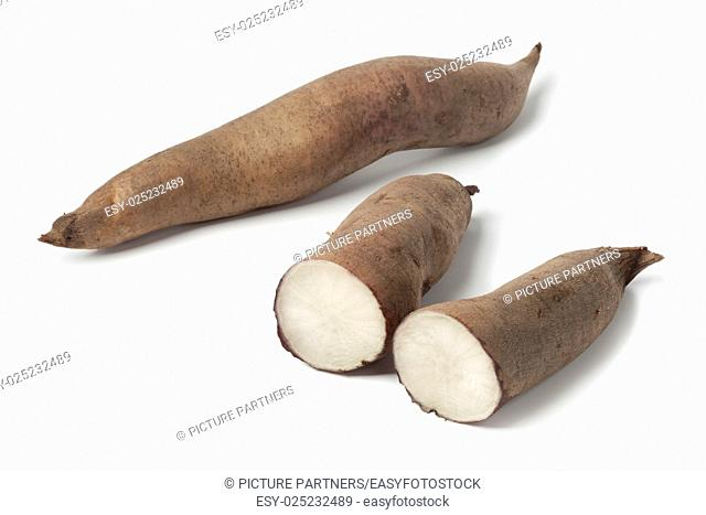 Fresh whole and half yacon roots on white background