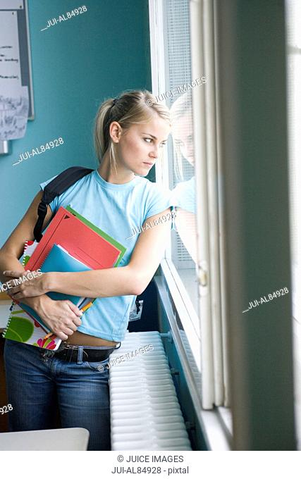 Female teenage student looking out window in classroom