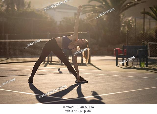 Woman doing stretching exercise in the tennis court