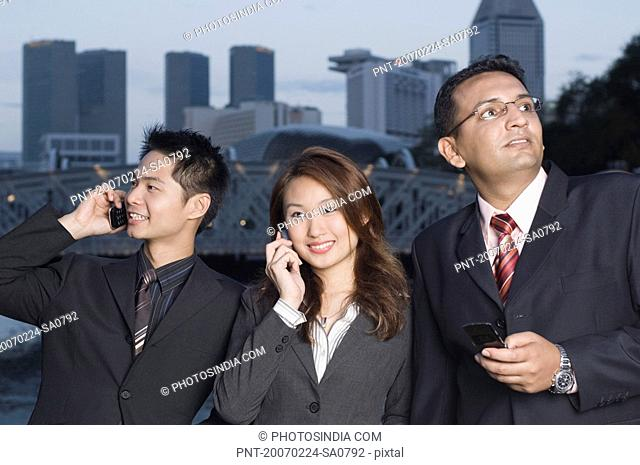 Two businessmen and a businesswoman standing together and using mobile phones, Singapore