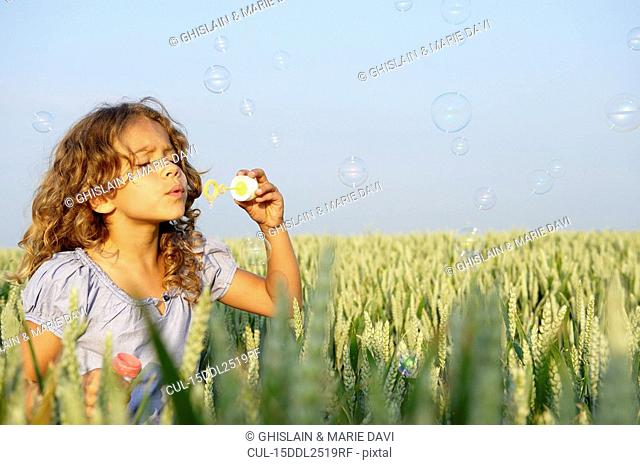 Girl blowing bubbles in a wheat field