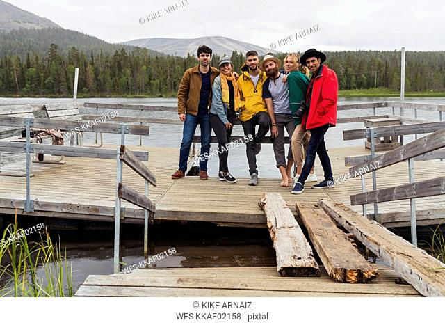 Finland, Lapland, portrait of friends standing on jetty at a lake