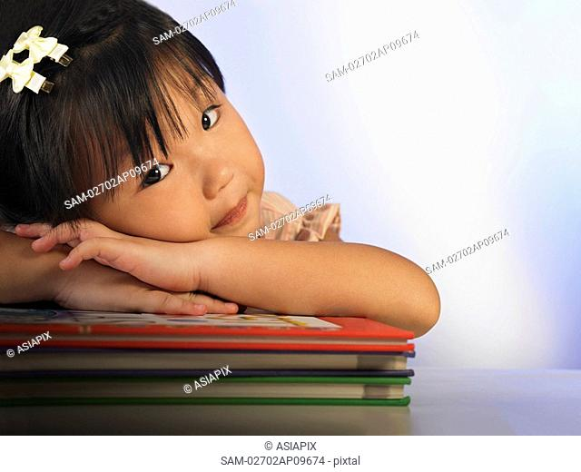 little girl resting her head on a stack of books