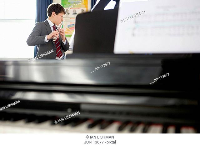 High school student playing flute in music class behind piano