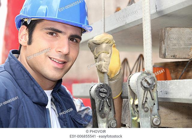 Tradesman standing next to a hoist