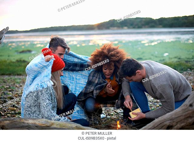 Four adult friends igniting campfire on beach
