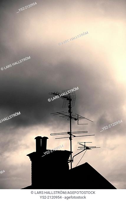 Silhouette of rooftop, chimney and antenna of old house with dark, mysterious and moody setting