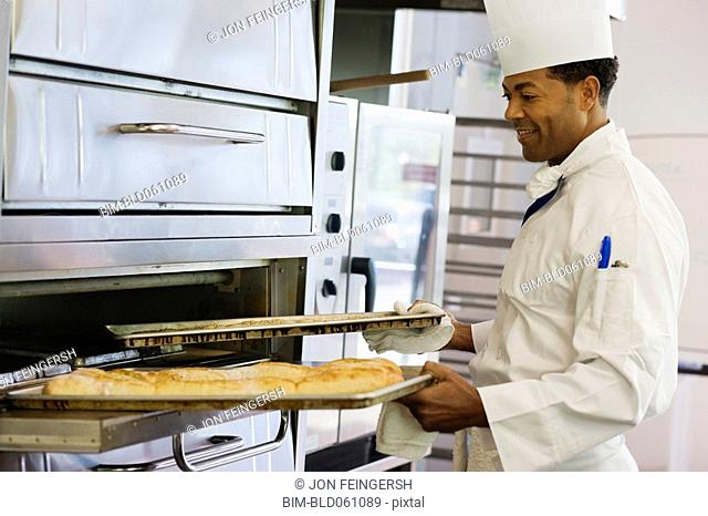 African male baker taking bread from oven
