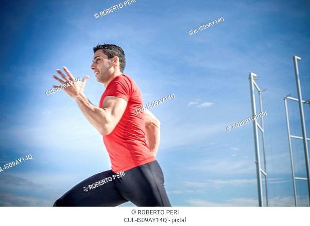 Young man sprinting against blue sky