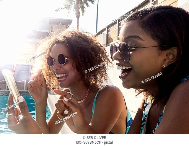 Friends using mobile phone by pool