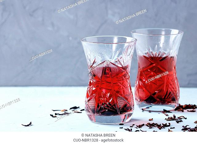 Two traditional asian style glasses with hibiscus tea karkade, served with dry hibiskus over blue and gray textured background. With space for text