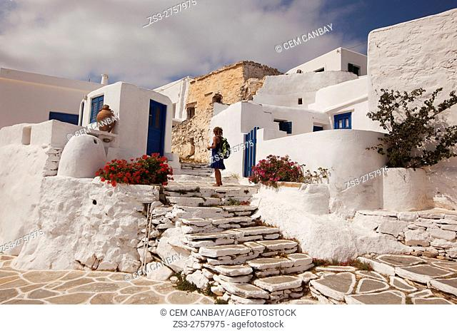 Woman in front of the whitewashed houses in the old town Chora or Chorio, Sikinos, Cyclades Islands, Greek Islands, Greece, Europe