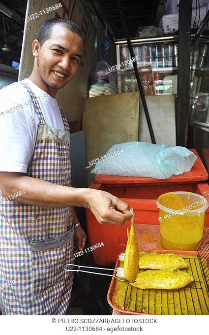 Kuala Lumpur (Malaysia): a man grilling some fish at a stall by Chinatown