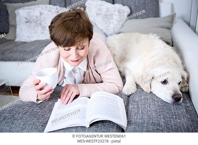 Senior woman lying on couch, reading book with dog by her side