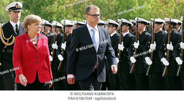 German Chancellor Angela Merkel (front L) receives Finland's Prime Minister Juha Sipila with a military salute at the Federal Chancellery in Berlin, Germany