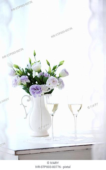 Close-up of wine glasses with flower vase