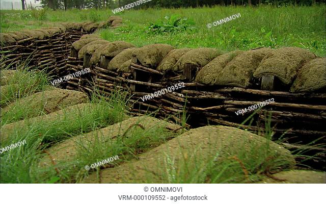 First World War trench with sand bags, wooden posts, wooden planks and green fields
