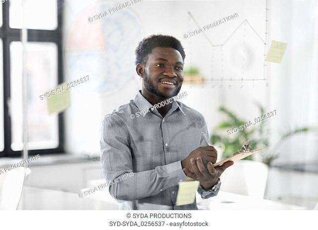 businessman with clipboard at office glass wall