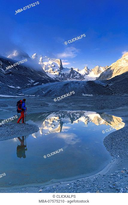 Hikers looks sunrise from a pond at Forno Glacier, Forno Valley, Maloja Pass, Engadin, Graubünden, Switzerland, Europe