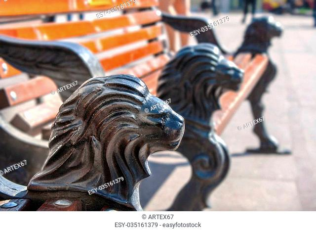 a park bench with cast iron legs in the form of a lion's head