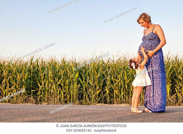 Pregnant mother and her little daughter expecting newborn brother. Country road between cornfields
