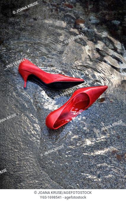 a pair of red women's shoes on the beach in water