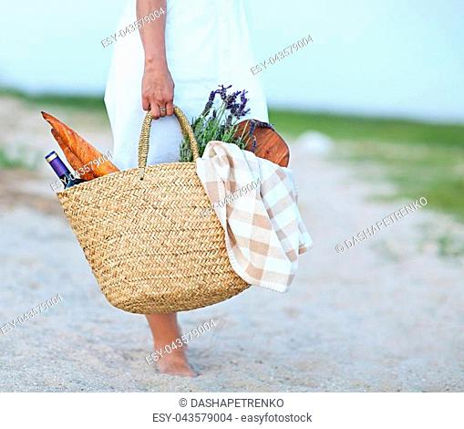 Young woman holding picnic basket with bottle of wine and baguette on sand beach