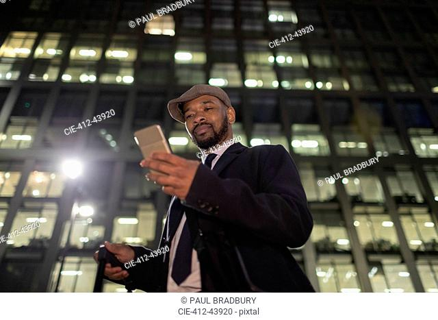 Businessman with smart phone standing below urban highrise at night