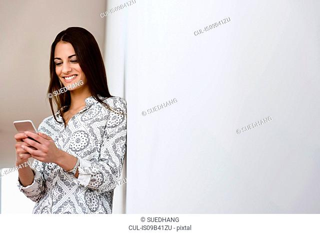 Young businesswoman leaning against office wall looking at smartphone