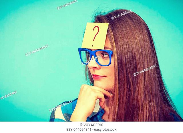 Thinking woman with big nerdy eyeglasses and question mark on forehead. Creating new idea, studying and education concept