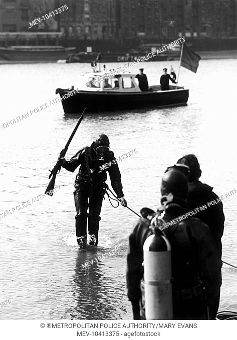 A diver of the Underwater Search Unit of the Metropolitan Police recovering a rifle from the River Thames, London. A Thames Division launch can be seen on the...