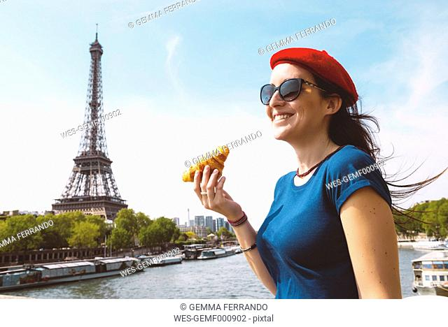 France, Paris, woman with croissant standing in front of Seine river and Eiffel Tower