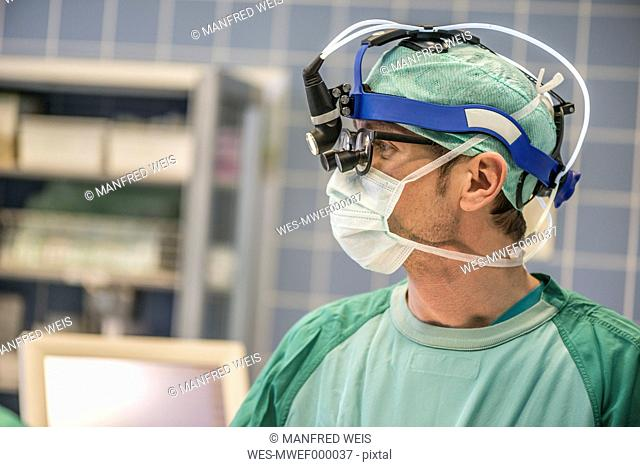 Heart surgeon with head lamp in operating room