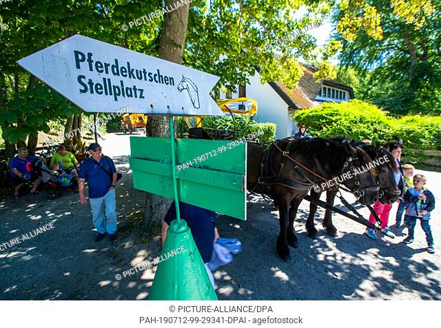 11 July 2019, Mecklenburg-Western Pomerania, Kloster: Holidaymakers wait at the horse-drawn carriage parking lot on the Baltic Sea island of Hiddensee for the...