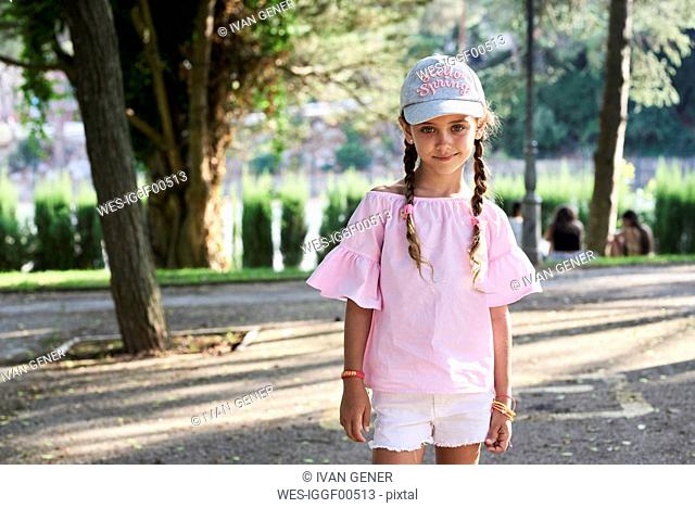 Portrait of smiling little girl with braids and cap