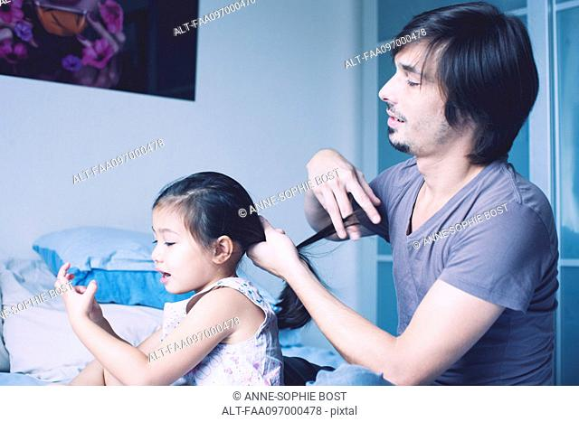 Father putting daughter's hair in ponytail