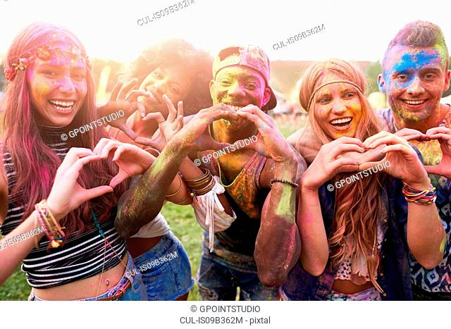 Portrait of group of friends at festival, covered in colourful powder paint, making heart shapes with hands