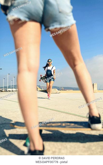 Happy young woman with longboard and headphones on beach promenade