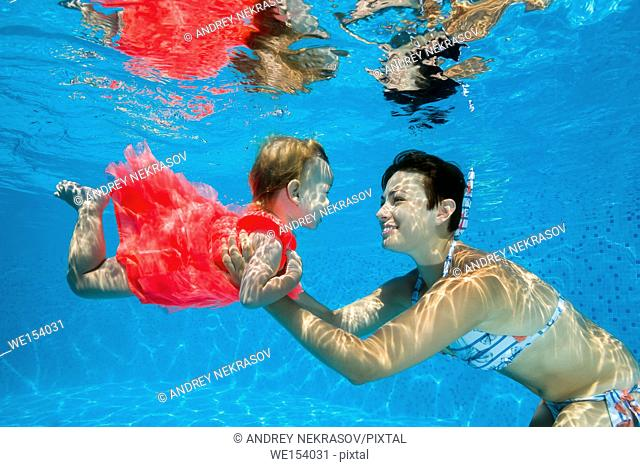 Mom with little daughter under water in pool