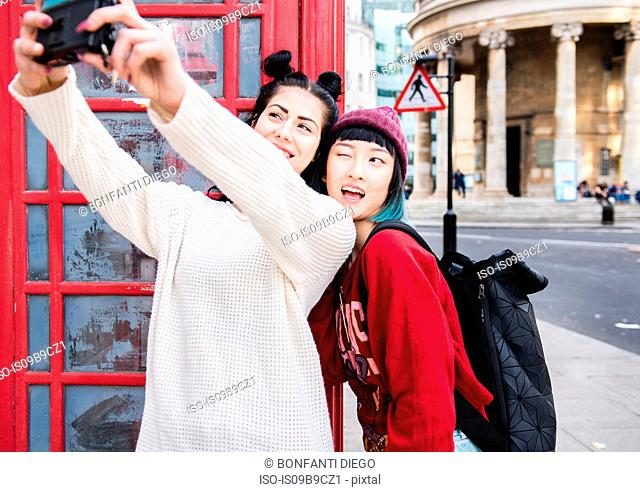 Two young stylish women taking selfie by red phone box, London, UK